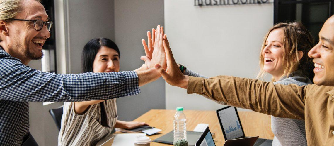 ארבעה אנשים לוחצים ידיים בישיבה ליד שולחן